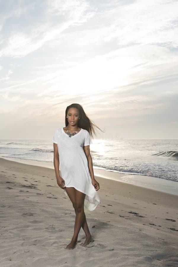 Mujer afroamericana joven imponente en la playa en la salida del sol fotografía de archivo