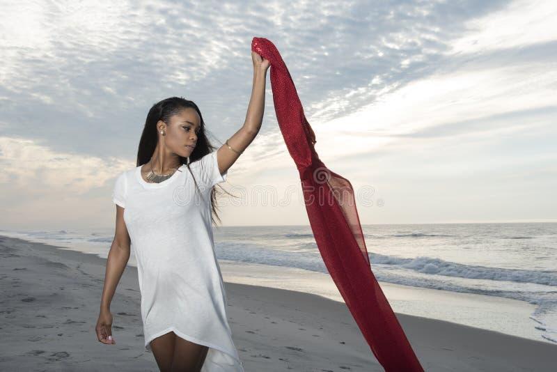 Mujer afroamericana joven imponente en la playa en la salida del sol fotos de archivo libres de regalías