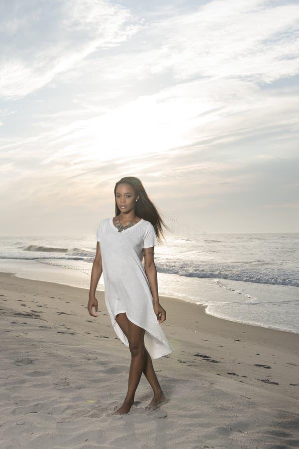 Mujer afroamericana joven imponente en la playa en la salida del sol imagen de archivo libre de regalías