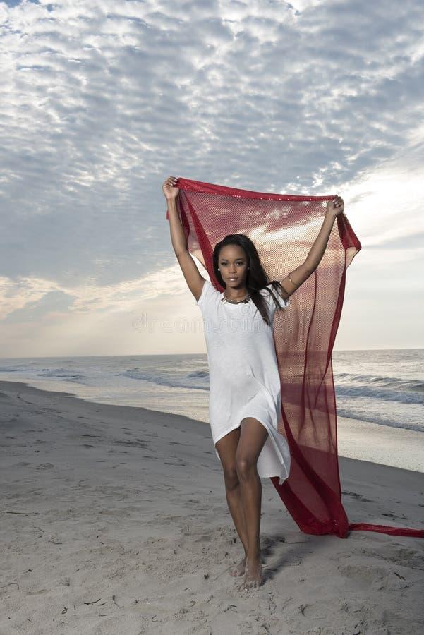 Mujer afroamericana joven imponente en la playa en la salida del sol fotos de archivo