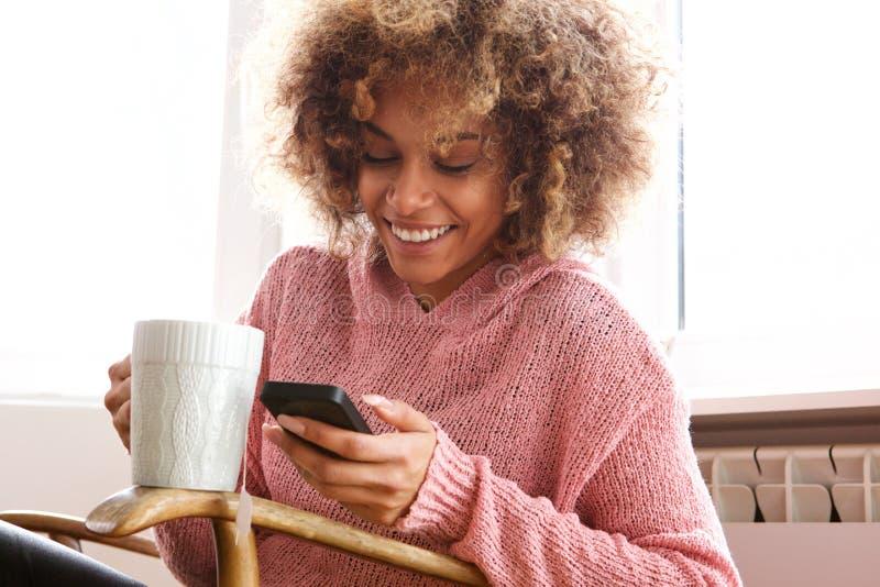 Mujer afroamericana joven que bebe la taza de café caliente y que mira el teléfono móvil imagenes de archivo