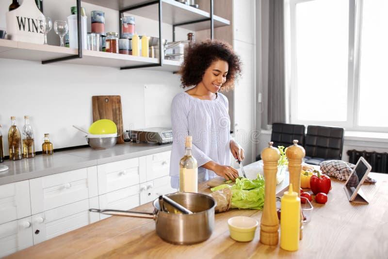 Mujer afroamericana joven que cocina en cocina imagen de archivo libre de regalías