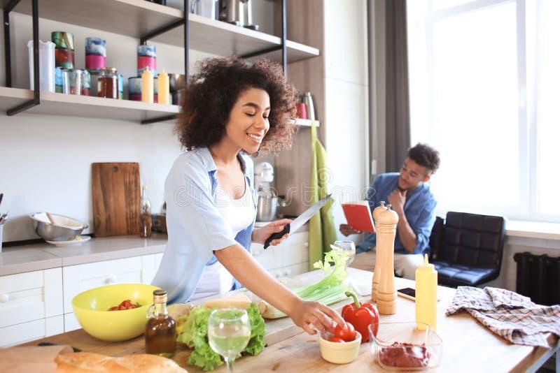 Mujer afroamericana joven que cocina la comida y su libro de la receta de la lectura del novio en cocina fotografía de archivo libre de regalías