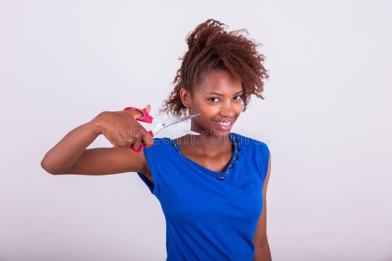 Mujer afroamericana joven que corta su pelo afro muy rizado con s foto de archivo