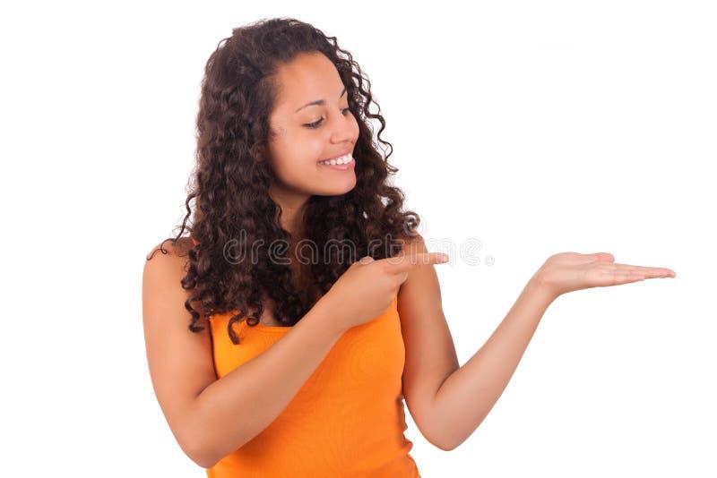 Mujer afroamericana joven que exhibe algo imagen de archivo libre de regalías