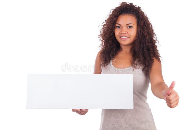 Mujer afroamericana joven que lleva a cabo la muestra en blanco aislada en un wh imagen de archivo libre de regalías