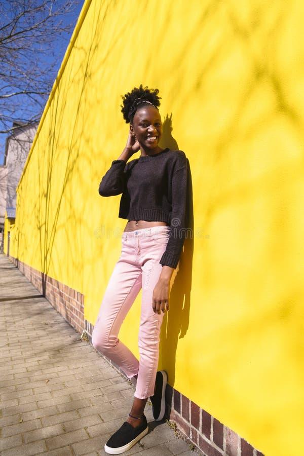 Mujer afroamericana joven que lleva vaqueros rosados fotos de archivo libres de regalías
