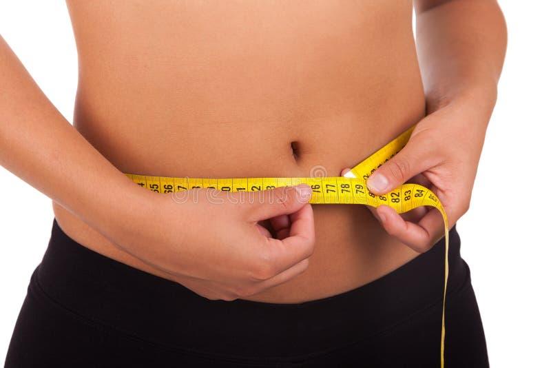 Mujer afroamericana joven que mide su vientre imagen de archivo
