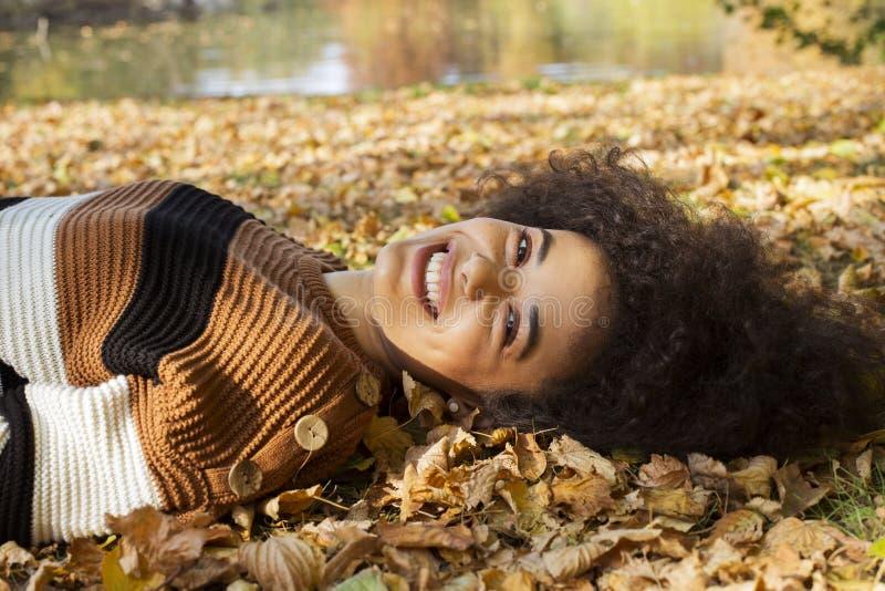 Mujer afroamericana joven que miente en las hojas oto?ales en parque soleado foto de archivo libre de regalías
