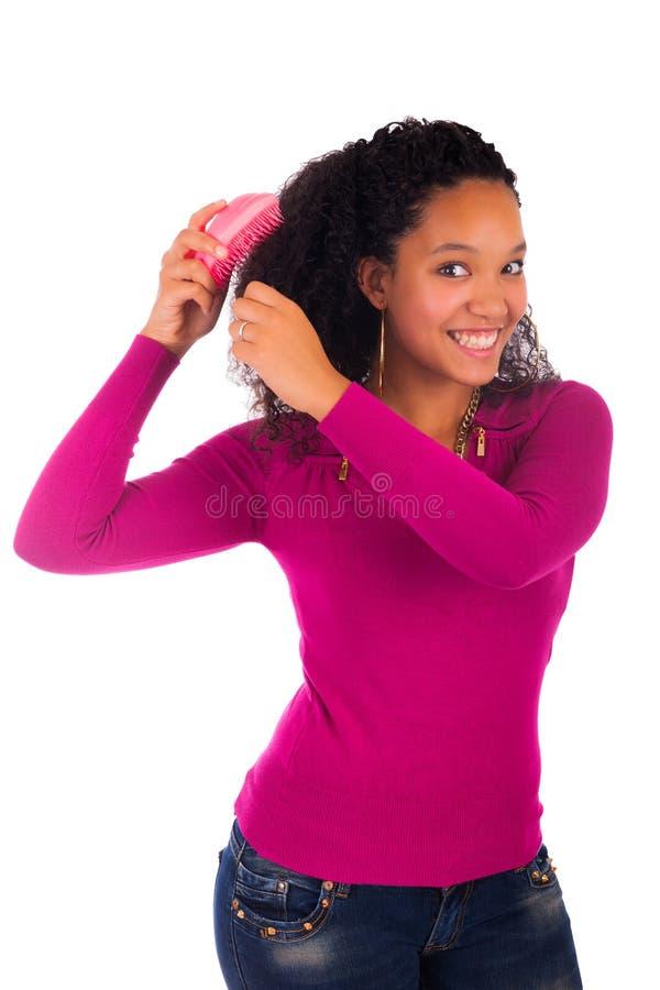 Mujer afroamericana joven que peina el pelo imágenes de archivo libres de regalías
