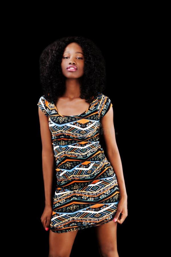 Mujer afroamericana joven que se coloca en fondo del negro del vestido imagenes de archivo
