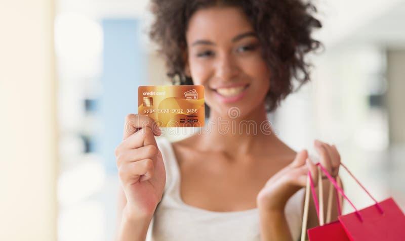 Mujer afroamericana joven que sostiene bolsos y la tarjeta de crédito coloridos fotos de archivo