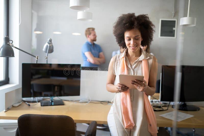 Mujer afroamericana joven que trabaja con la tableta en oficina fotos de archivo libres de regalías