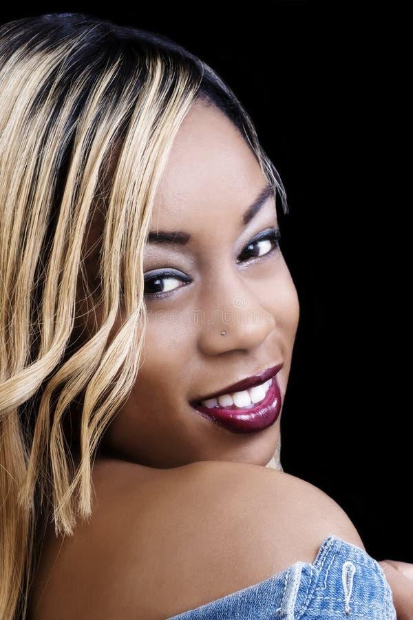 Mujer afroamericana joven sonriente que mira sobre hombro fotografía de archivo libre de regalías