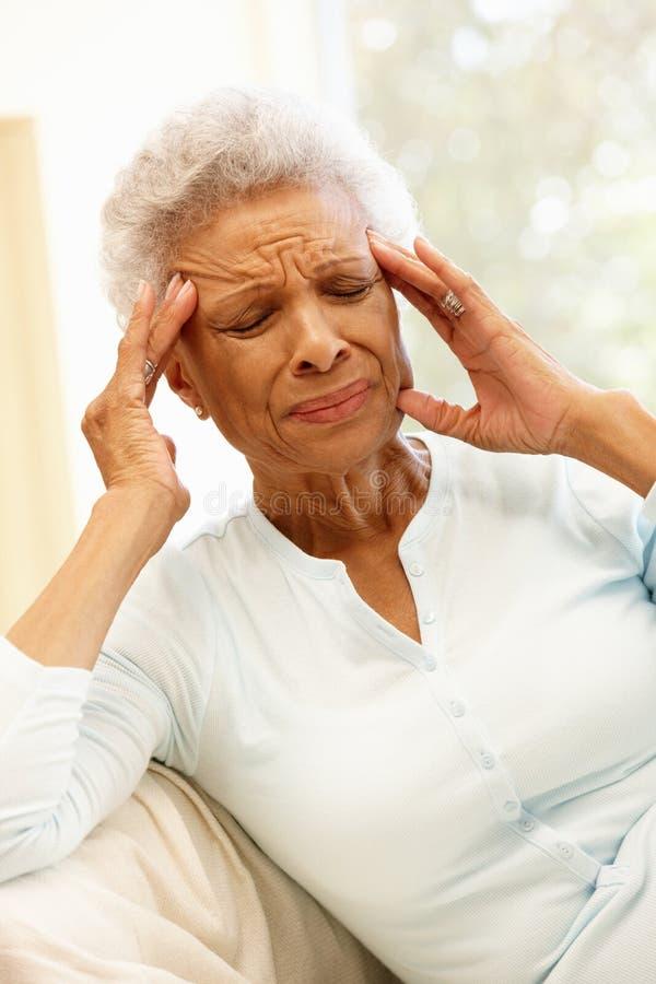 Mujer afroamericana mayor con dolor de cabeza foto de archivo