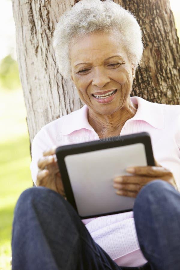 Mujer afroamericana mayor en parque usando la tableta fotografía de archivo