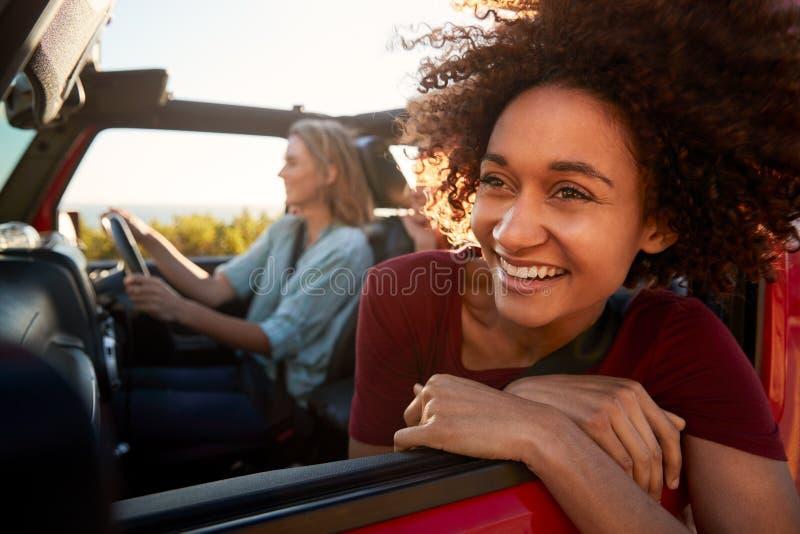 Mujer afroamericana milenaria en un viaje por carretera con los amigos, inclinándose fuera de la ventanilla del coche, cierre par fotografía de archivo libre de regalías