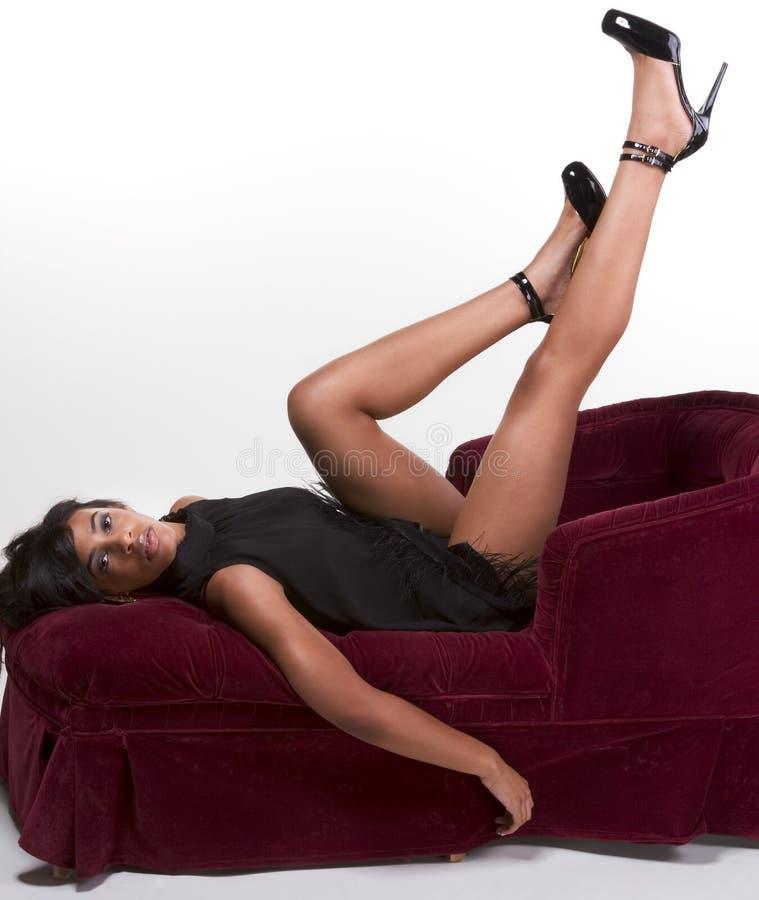 Mujer afroamericana modelo atractiva en el sofá rojo imágenes de archivo libres de regalías