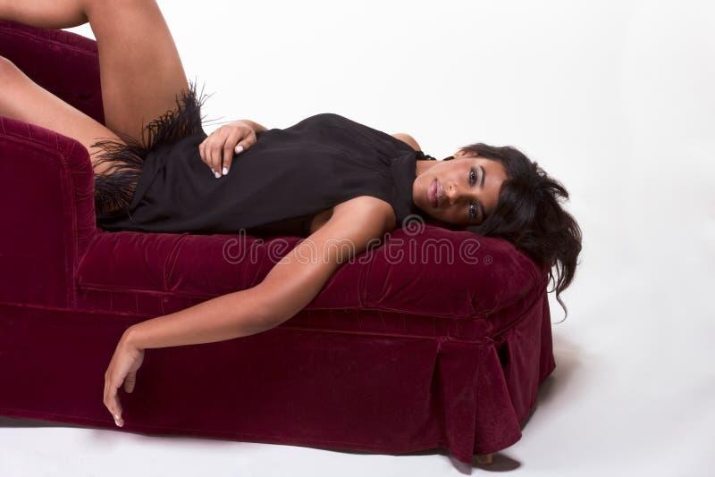 Mujer afroamericana modelo atractiva en el sofá rojo foto de archivo libre de regalías