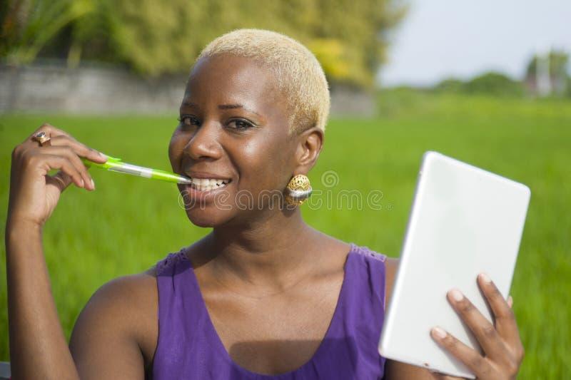 Mujer afroamericana negra acertada atractiva y feliz joven que trabaja con el cojín digital de la tableta al aire libre en smili  fotografía de archivo