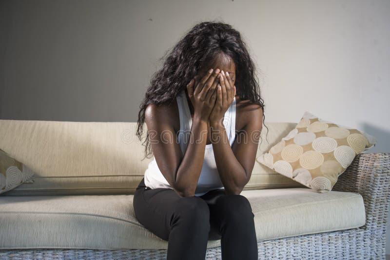 Mujer afroamericana negra atractiva y triste joven que sienta en casa las sensaciones presionadas del sofá del sofá ansiosas y su imágenes de archivo libres de regalías