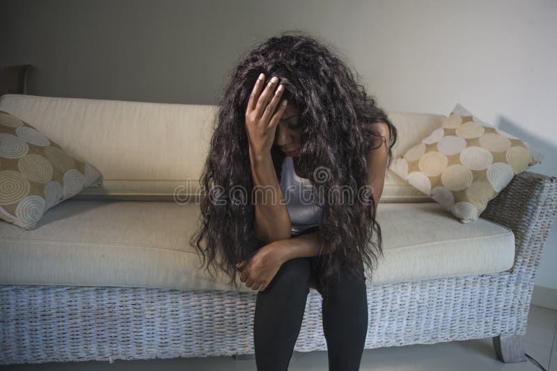 Mujer afroamericana negra atractiva y triste joven que sienta en casa las sensaciones presionadas del sofá del sofá ansiosas y su foto de archivo