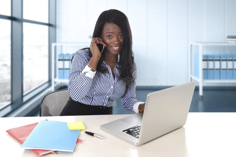 Mujer afroamericana negra de la pertenencia étnica que trabaja en el ordenador portátil del ordenador en la sonrisa del escritori imagenes de archivo