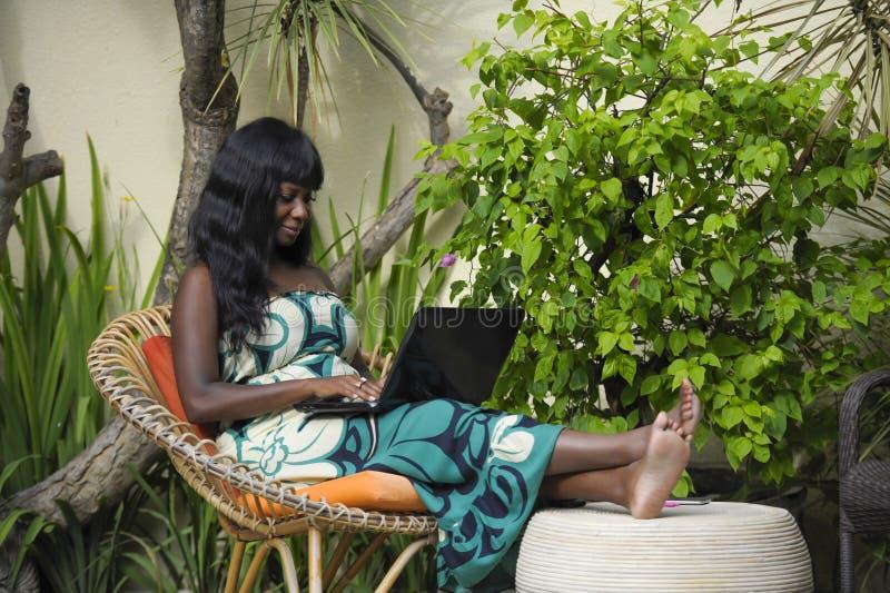 Mujer afroamericana negra feliz en el vestido elegante que trabaja en el chalet de lujo de la terraza con el ordenador portátil e fotografía de archivo libre de regalías