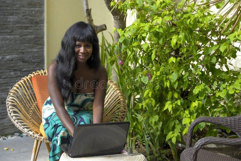 Mujer afroamericana negra feliz en el vestido elegante que trabaja en el chalet de lujo de la terraza con el ordenador portátil e foto de archivo