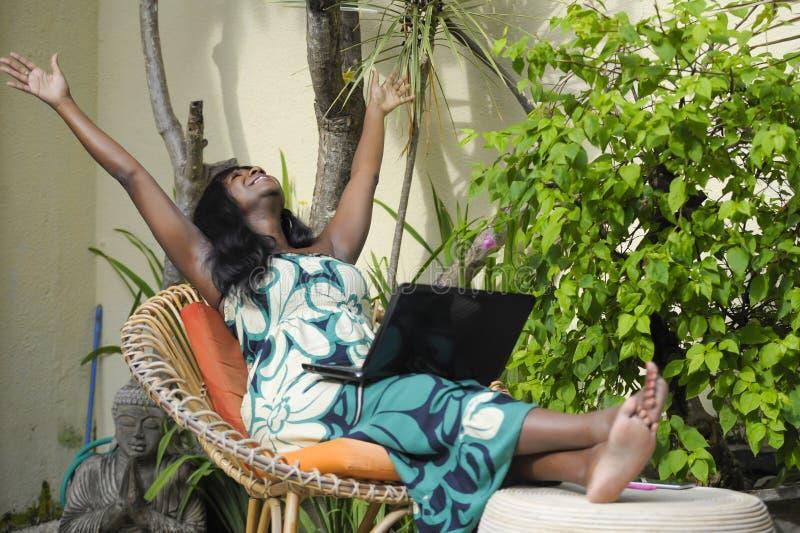 Mujer afroamericana negra feliz en el vestido elegante que trabaja en el chalet de lujo de la terraza con el ordenador portátil e imagenes de archivo