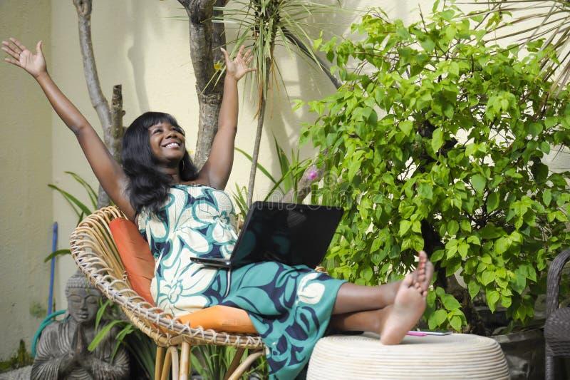 Mujer afroamericana negra feliz en el vestido elegante que trabaja en el chalet de lujo de la terraza con el ordenador portátil e imágenes de archivo libres de regalías