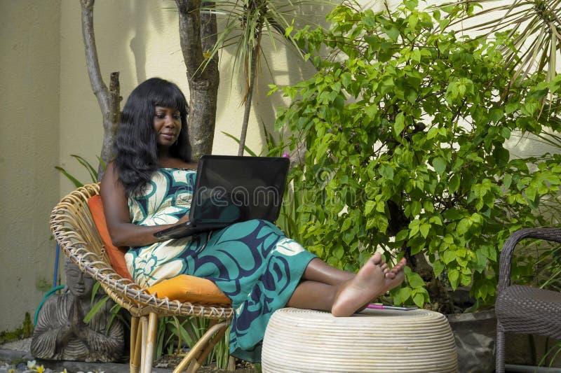 Mujer afroamericana negra feliz en el vestido elegante que trabaja en el chalet de lujo de la terraza con el ordenador portátil e foto de archivo libre de regalías