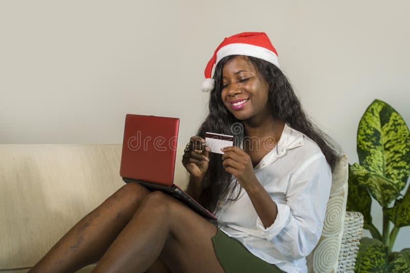 Mujer afroamericana negra feliz y atractiva joven en el sombrero de Santa Claus que sostiene el regalo de Navidad y el regalo o d imagen de archivo