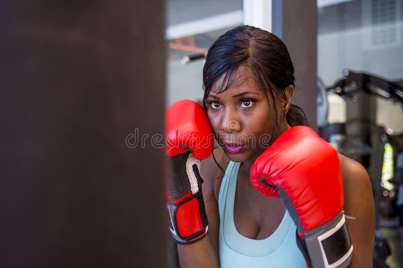 Mujer afroamericana negra resuelta atractiva y hermosa joven en el entrenamiento del gimnasio sudoroso en el bolso pesado que per foto de archivo libre de regalías