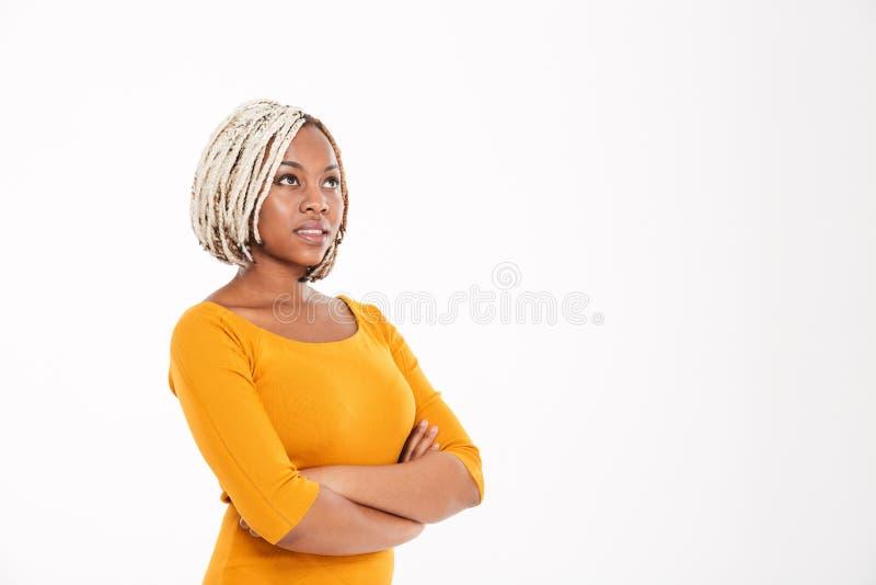 Mujer afroamericana pensativa con los brazos cruzados y que miran para arriba imagen de archivo