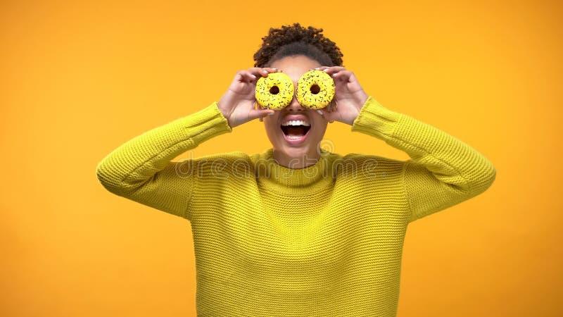 Mujer afroamericana positiva que lleva a cabo el frente de ojos, humor juguet?n de los anillos de espuma, bromeando fotos de archivo