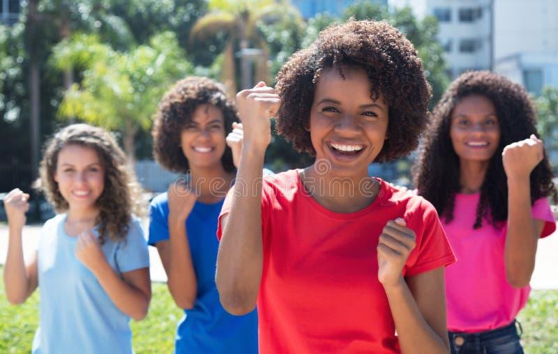 Mujer afroamericana que anima con el pequeño grupo de muchachas latinas y caucásicas foto de archivo libre de regalías