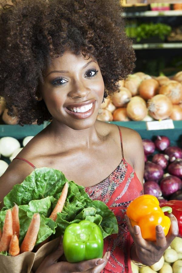 Mujer afroamericana que celebra los paprikas y las verduras en el supermercado fotos de archivo
