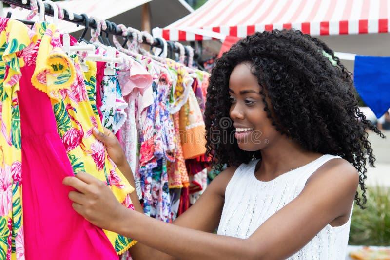 Mujer afroamericana que compra ropa colorida en el mercado fotografía de archivo