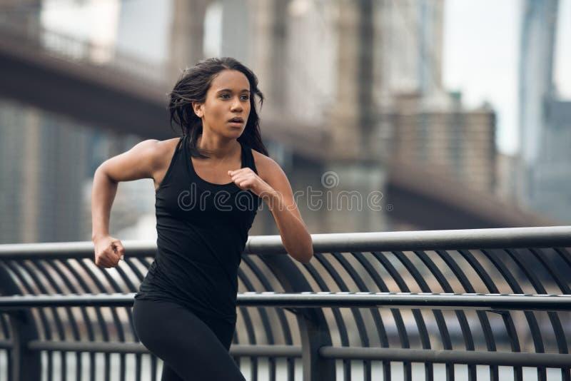 Mujer afroamericana que corre en New York City en la mañana imagen de archivo