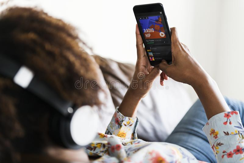 Mujer afroamericana que disfruta de ocio de la música en casa y de concepto de la música imágenes de archivo libres de regalías