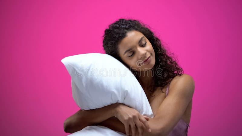 Mujer afroamericana que duerme profundamente en la almohada cómoda, buena descansando concepto foto de archivo