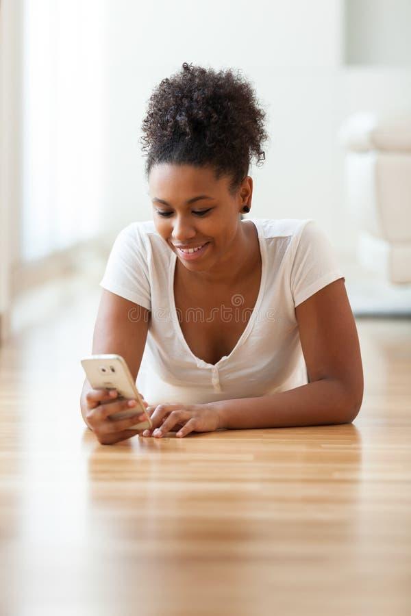 Mujer afroamericana que envía un mensaje de texto en un teléfono móvil fotos de archivo libres de regalías