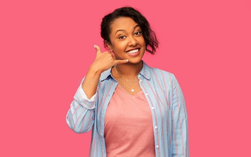 Mujer afroamericana que hace gesto de la llamada de teléfono imagen de archivo