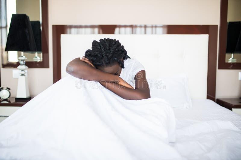 Mujer afroamericana que mira dormido cansado en la cama en casa foto de archivo libre de regalías