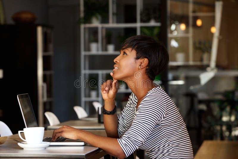 Mujer afroamericana que se sienta en el café con el ordenador portátil fotos de archivo libres de regalías