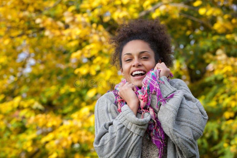 Mujer afroamericana que sonríe con el suéter y la bufanda en otoño imagenes de archivo
