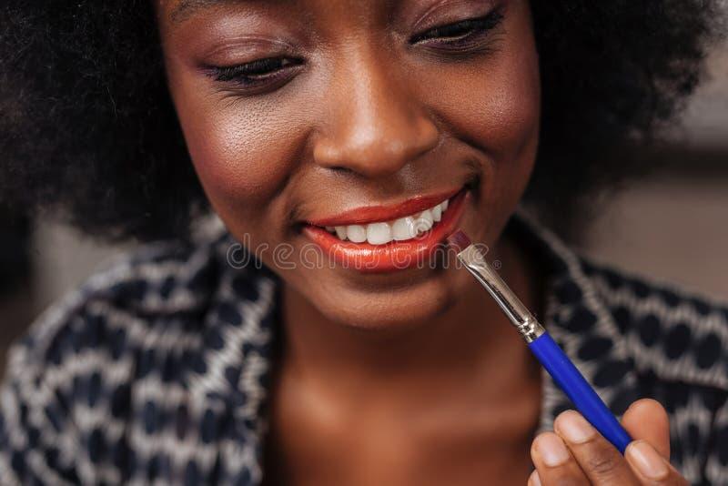 Mujer afroamericana que sorprende con el pelo rizado que intenta un nuevo color de la barra de labios fotos de archivo libres de regalías