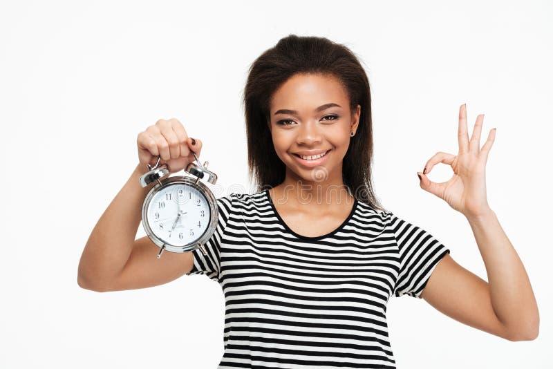 Mujer afroamericana que sostiene el despertador y que muestra gesto aceptable imágenes de archivo libres de regalías