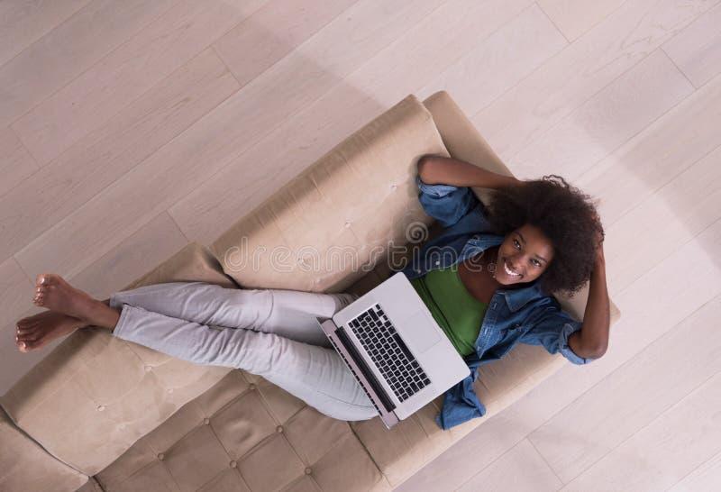 Mujer afroamericana que usa el ordenador portátil en la opinión superior del sofá fotos de archivo